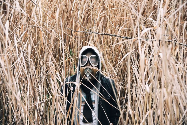 Portrait Of Man In Protective Clothing At Grassy Field
