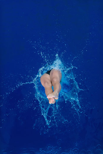 High Angle View Of Mid Adult Woman Wearing Bikini While Jumping In Swimming Pool