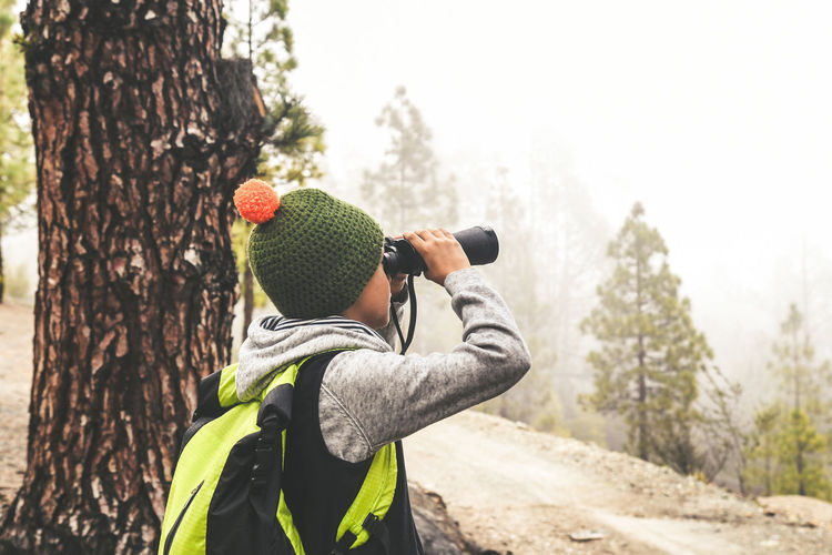 Child seen from behind with fluorescent backpack looks binoculars exploring nature of wild mountain forest. Family adventure discovery outdoor life. Young boy looking at the future. Positive concept Tree Plant Hat Tree Trunk Real People Clothing Trunk Nature One Person Land Men Day Focus On Foreground Leisure Activity Winter Knit Hat Lifestyles Holding Activity Standing Warm Clothing Outdoors