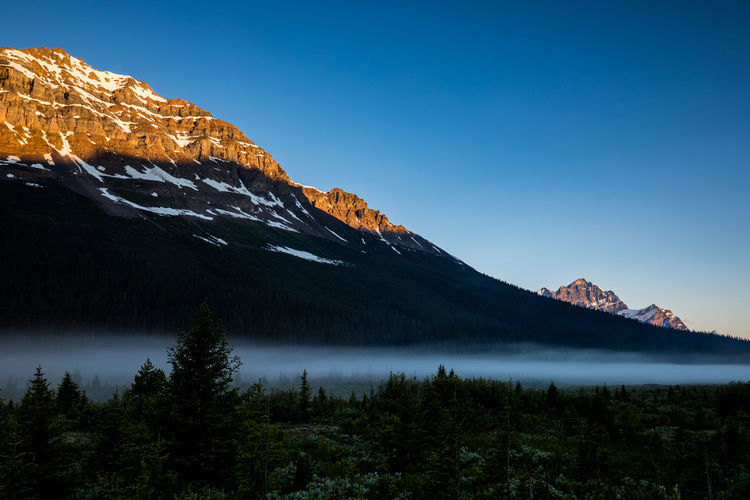 Beautiful Mount Jimmy Simpson at Sunrise. On the scenic Icefields Parkway. In the Rocky Mountains of Alberta Canada, Banff National Park Mountain Scenics - Nature Tranquility Tranquil Scene Beauty In Nature Sky Water Mountain Range Non-urban Scene Tree Lake No People Idyllic Nature Plant Cold Temperature Remote Snowcapped Mountain Formation Mountain Peak
