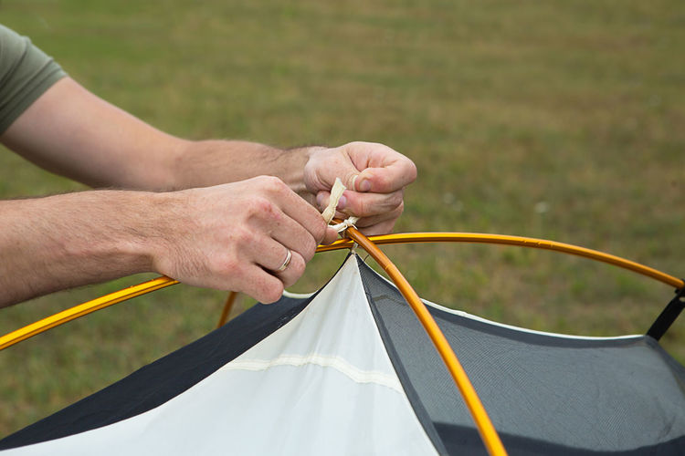 Aluminum mounting arcs for the installation of a tourist yellow tent in the hand close-up.