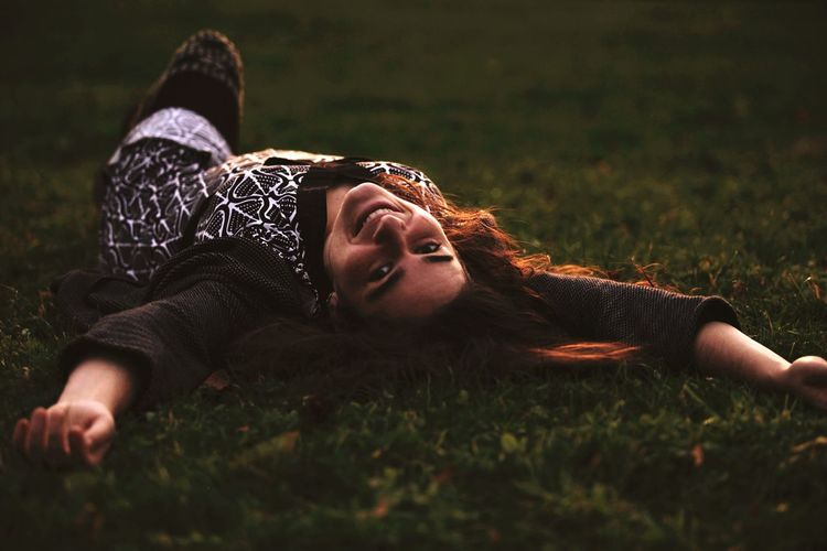 Portrait of beautiful woman lying on grass at park during sunset