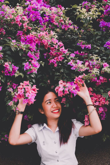 Smiling young woman standing by pink flowering plants