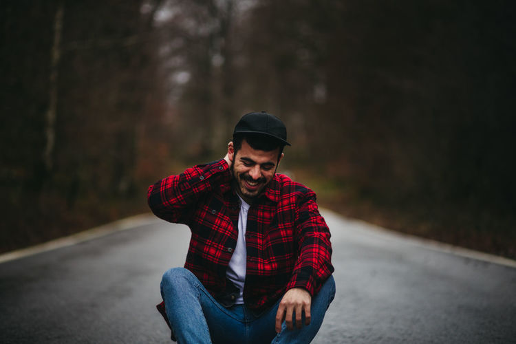 Young man looking away while sitting on road