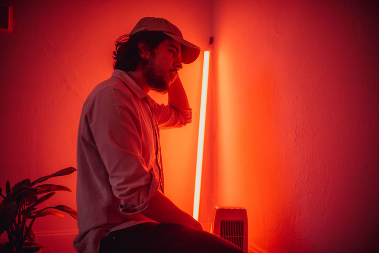 Side view of bearded man wearing cap in illuminated room