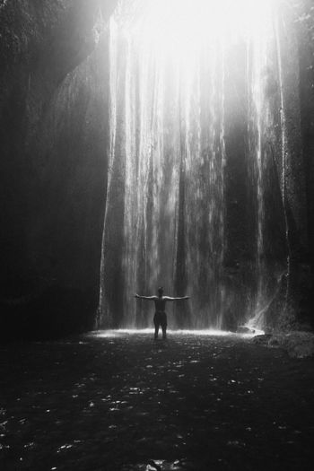 A man stands right in front of the Tukad Cepung waterfall. Arms Outstretched Arms Raised Beauty In Nature Day Flowing Water Forest Full Length Human Arm Land Leisure Activity Lifestyles Nature One Person Outdoors Real People Rear View Silhouette Standing Sunbeam Sunlight Tranquility Ubud Water Waterfall WoodLand Be Brave Moments Of Happiness Stay Out