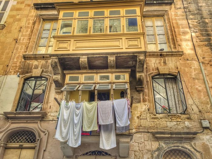 Facade with traditonal wooden balconies in Valetta, Malta Architecture Building Building Exterior Built Structure Clothesline Day Drying Hanging Laundry Low Angle View No People Outdoors Residential Building Window Wooden Balcony