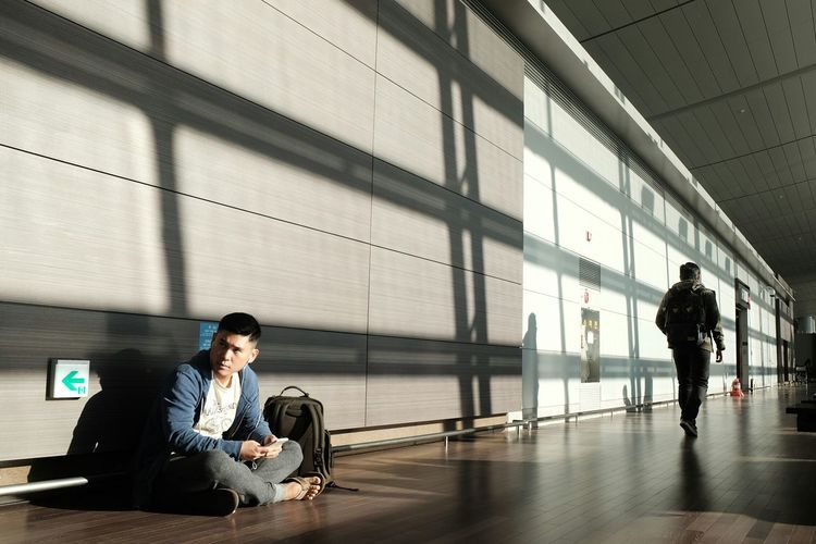 Mid Adult Man Sitting On Walkway At Airport