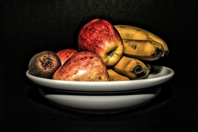 Close-Up Of Fruits In Plate Against Black Background