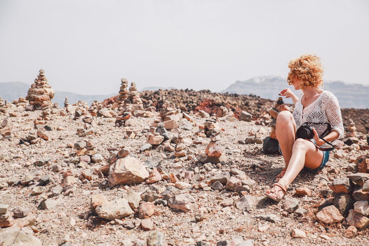 Woman Sitting On Rocky Landscape