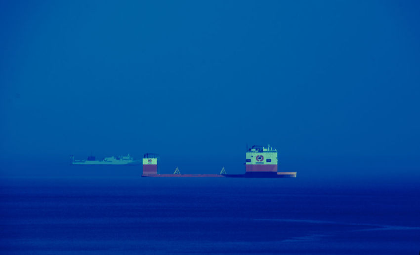 Boats in calm sea against clear blue sky