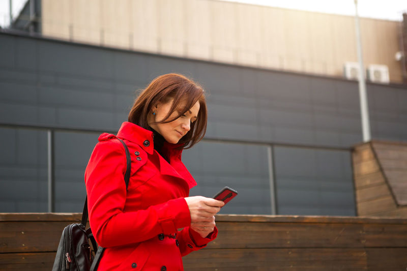 Young woman using mobile phone while standing at camera