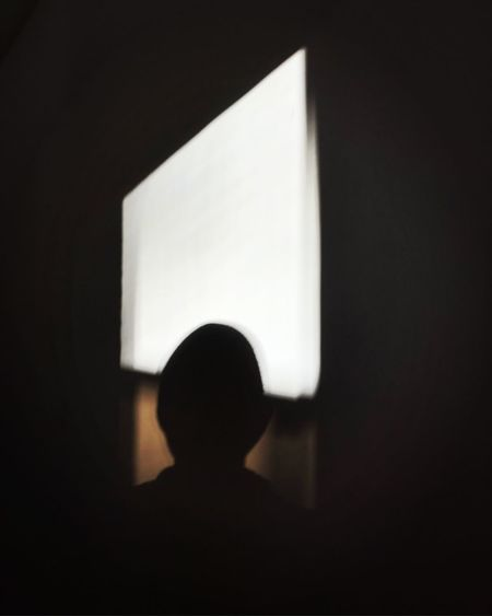 Rear view of silhouette boy against black background