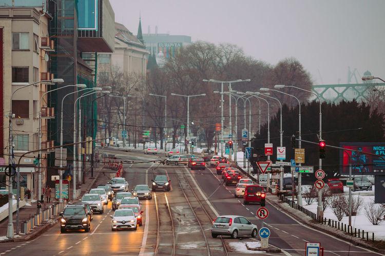 City Street Lamp Dusk Tram Lines Cars Building Lights Tracks Road Lanes Traffic Lights Traffic Signs