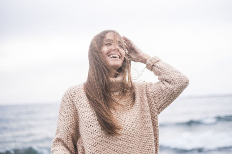 Portrait of happy young woman casual clothing close to the ocean waves. Wind in the hairs Sea Water One Person Hair Long Hair Hairstyle Waist Up Young Adult Front View Leisure Activity Sky Casual Clothing Happiness Nature Land Smiling Emotion Horizon Over Water Outdoors Warm Clothing Window Standing Cheerful 25-29 Years Sun