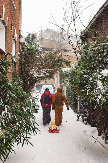 Rear view of women walking on snow during winter