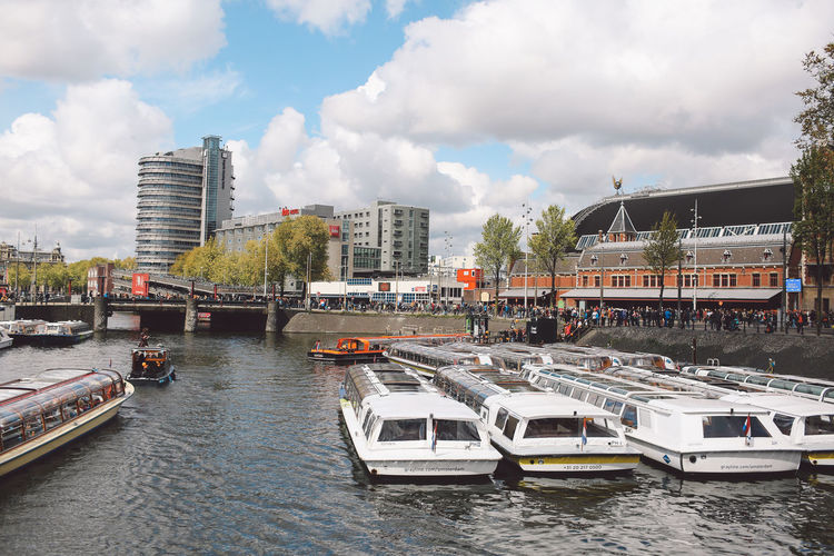 Boats moored in canal by buildings against cloudy sky