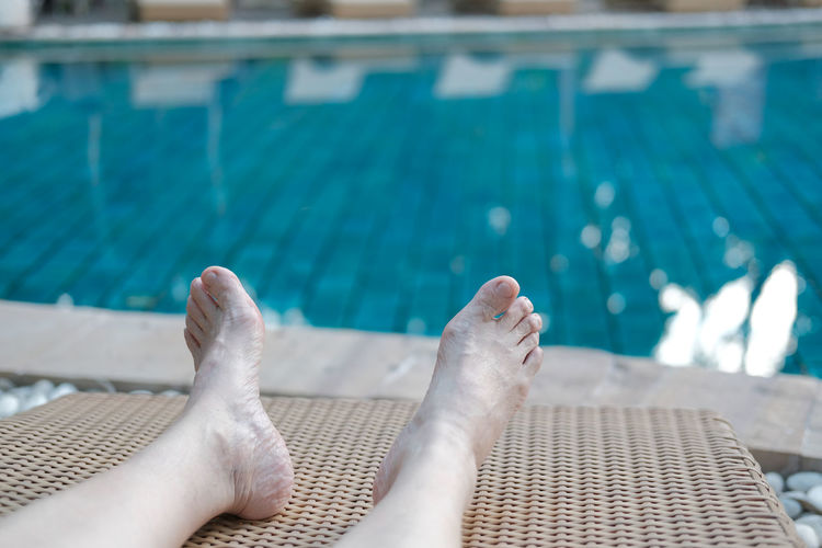 Low section of person relaxing at swimming pool