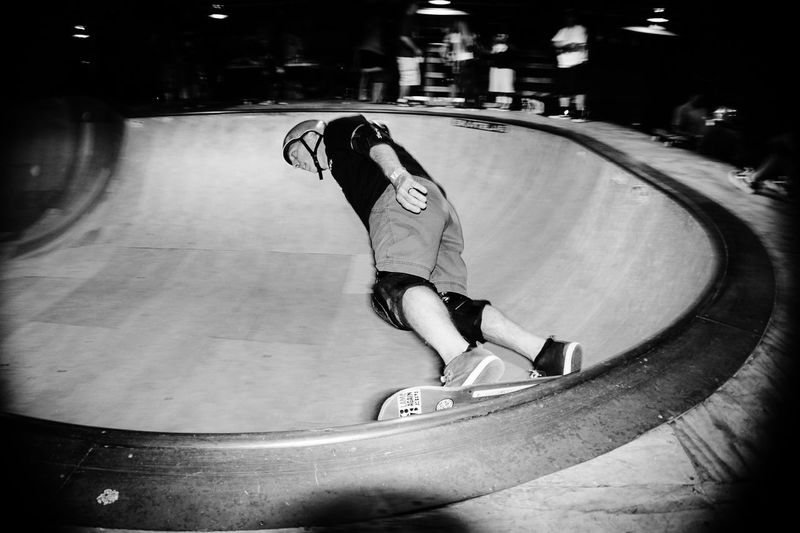 Midsection of man skateboarding on skateboard at night