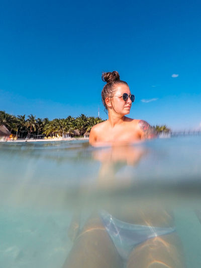Young woman swimming in sea against blue sky