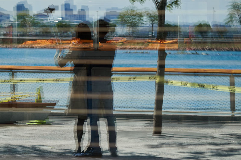 reflection of young couple enjoying the view Adult Architecture Blurred Motion Building Exterior Built Structure City Day Full Length Lifestyles Motion Nature Outdoors People Real People Sky Standing Water The Street Photographer - 2017 EyeEm Awards Live For The Story