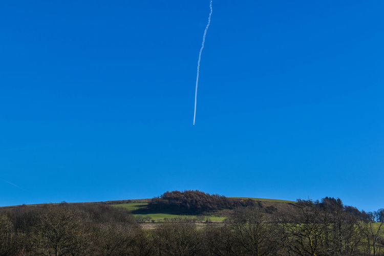 Low angle view of vapor trail against clear blue sky
