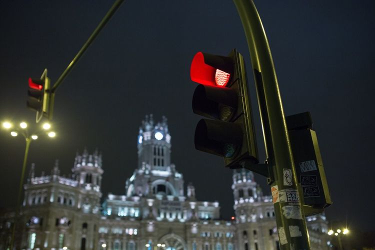 Low angle view of red light by plaza de cibeles at night
