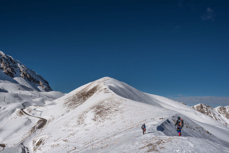 People climbing on snowcapped mountain against clear sky