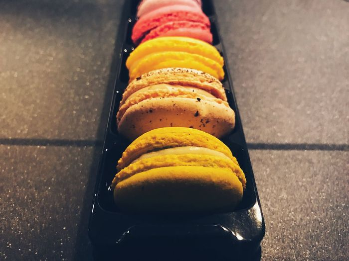 High angle view of multi colored macaroons in box on table