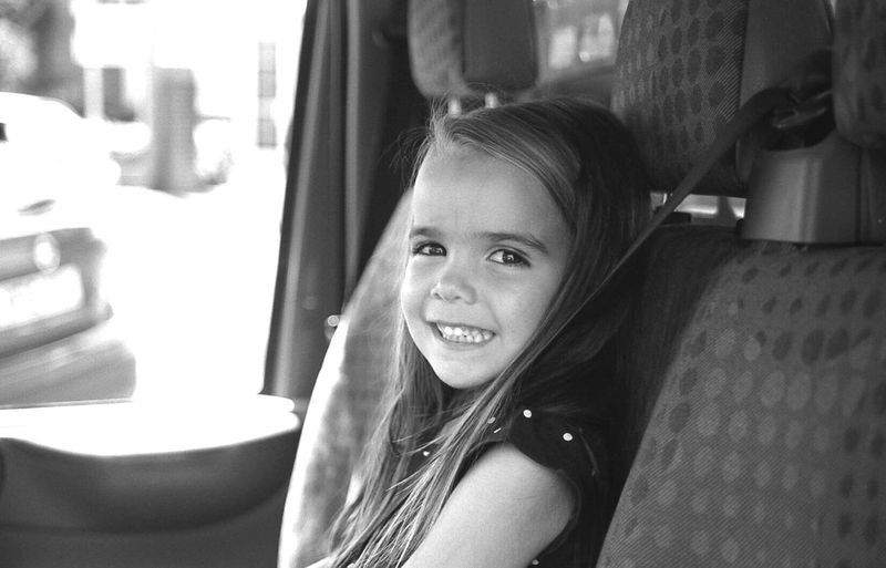 Side view portrait of happy girl traveling in car