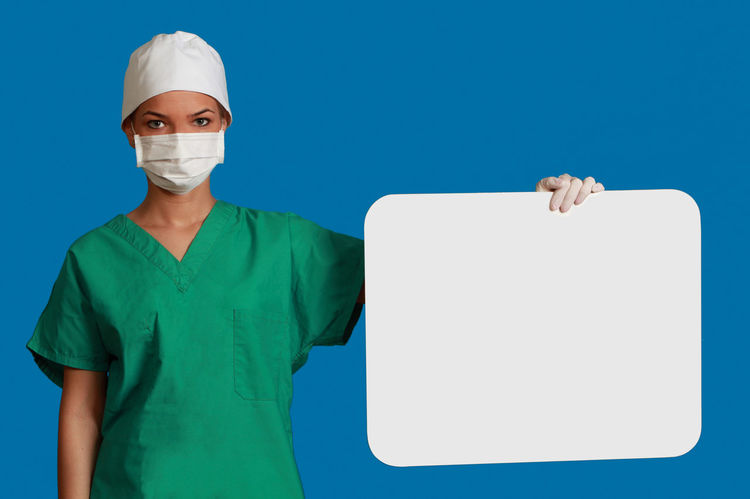 Young woman doctor keeping a white board, against a blue background. Copy Space Doctor  Healthcare Medicine Nurse White Board Adult Blue Blue Background Copy Space Green Color Healthcare And Medicine Keeping Looking At Camera Medical Cannabis Message One Person People Physician Placard Portrait Real People Studio Shot Surgical Mask