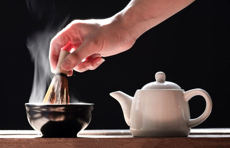 Hot matcha green tea on a black background Hand Hot Drink Smoke Zen Human Hand Food And Drink Cup Indoors  Hand Mug One Person Human Body Part Table Tea Drink Kitchen Utensil Close-up Tea - Hot Drink Coffee Cup Lifestyles Tea Cup Real People Holding Hot Drink