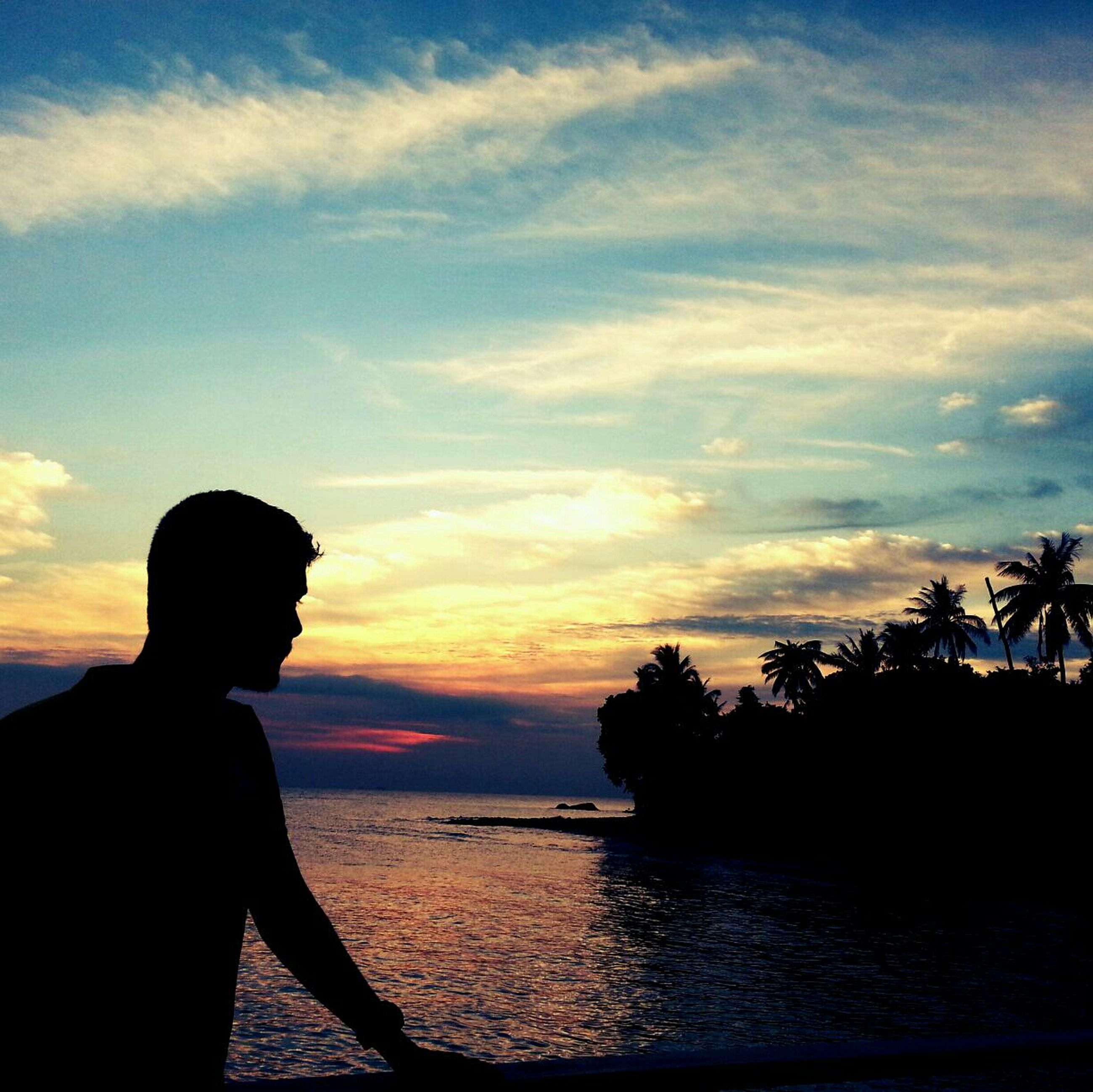sunset, silhouette, water, sea, sky, scenics, beauty in nature, horizon over water, lifestyles, tranquility, tranquil scene, leisure activity, standing, nature, idyllic, cloud - sky, orange color, men