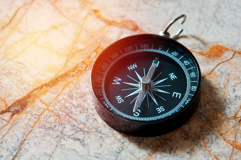 Close-up of navigational compass on cracked floor