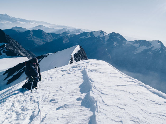 Hiker on snowcapped mountain against clear sky