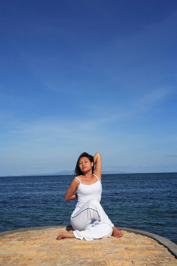Portrait of woman sitting on sea against blue sky