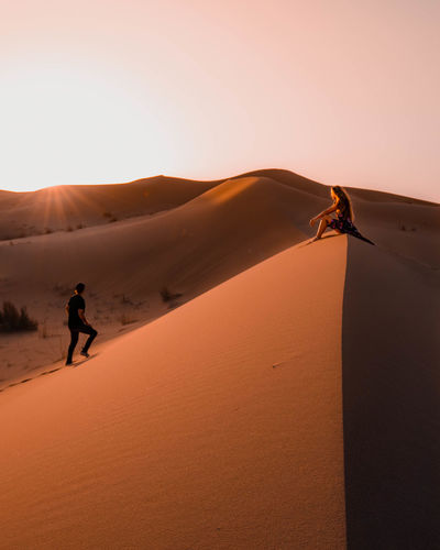 Couple sitting in the sahara desert in morocco during sunset