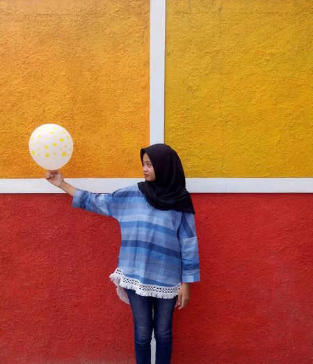 Woman Holding Balloon While Standing Against Wall