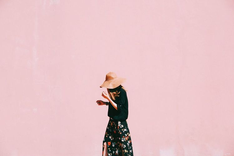 Woman Walking Against Pink Wall
