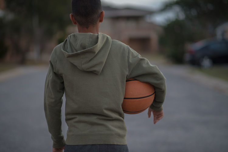 Rear view of boy holding basketball while standing on street