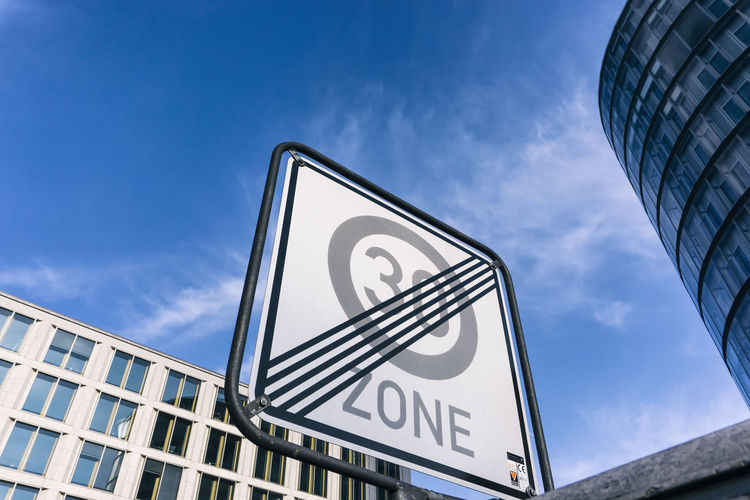 Low angle view of road sign in city against sky