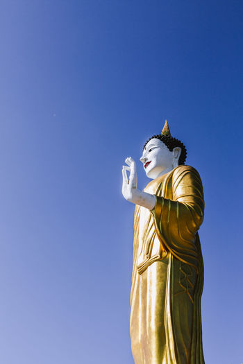 Sculpture Human Representation Statue Art And Craft Belief Representation Spirituality Male Likeness Sky Religion Blue No People Nature Gold Colored Craft Creativity Low Angle View Copy Space Idol Buddha Statue Buddist