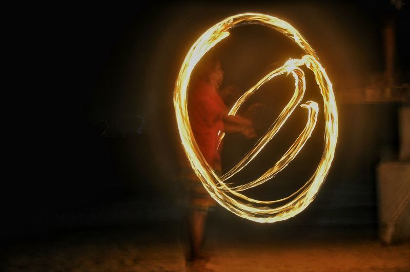 Blurred motion of man against illuminated lights at night