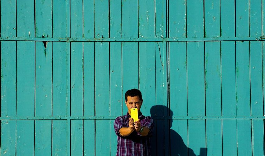 Man photographing through mobile phone while standing against blue wooden wall
