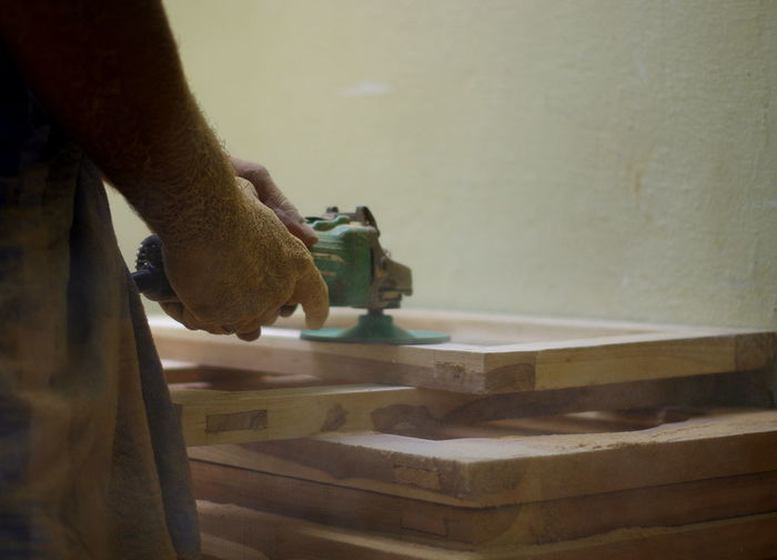 Midsection of carpenter working at carpentry workshop