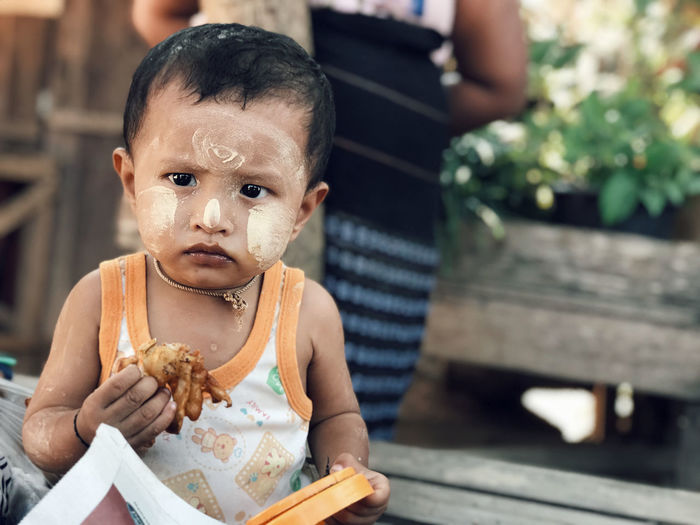 Portrait of cute baby girl holding food while sitting outdoors