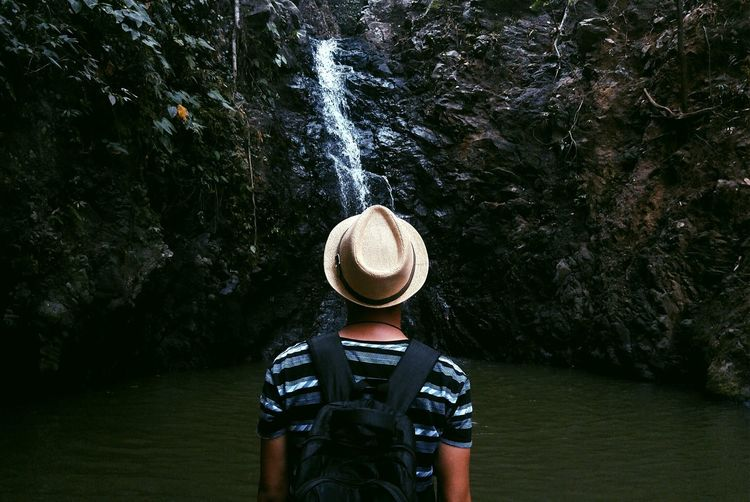 Man standing in front of waterfall in forest