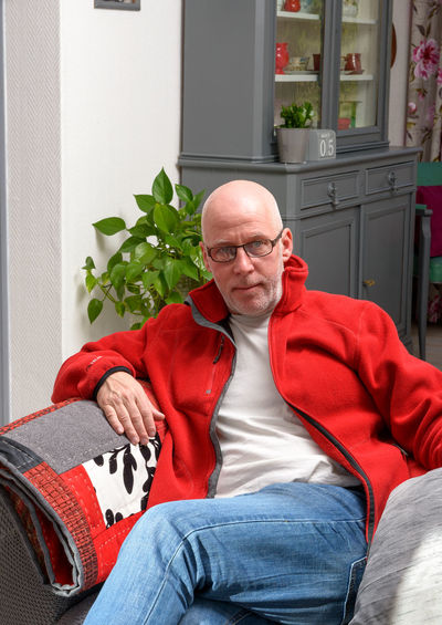 Portrait of bald mature man sitting on sofa at home