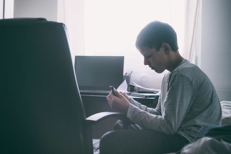 Side view of teenager using mobile phone and laptop