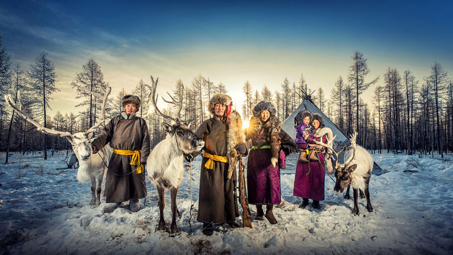 Portrait of family with reindeer on snow covered landscape during sunset
